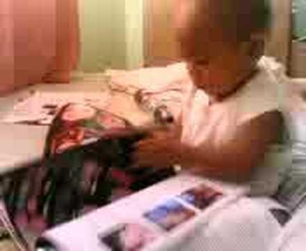 1 year old boy reading magazine