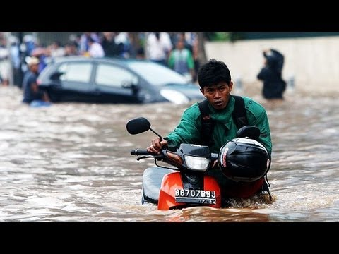 Floodwaters rise in Jakarta, as residents wade neck-deep