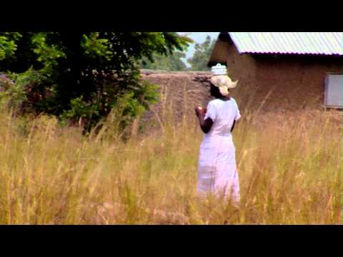 Royalty Free Stock Footage of African woman walking through a grassy field.