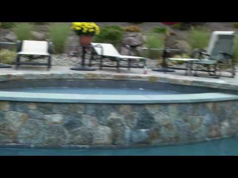 magnificient poolscape with inviting splash pool, stone hot tub, outdoor kitchen and more