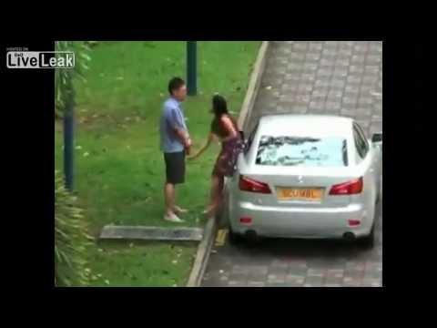 Djevojka muči svog dečka u javnosti pokraj svog automobila