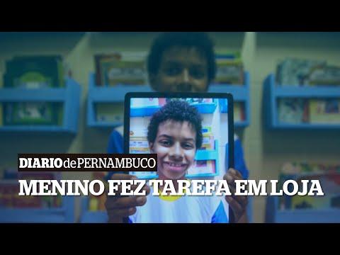 Menino utiliza tablet do mostruário de loja para fazer uma tarefa escolar