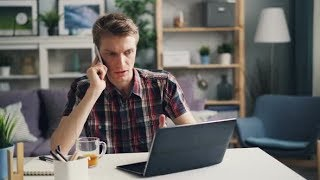 Irritated Guy Freelance Worker Is Talking on Mobile Phone and Using Laptop Expressing Negative  
