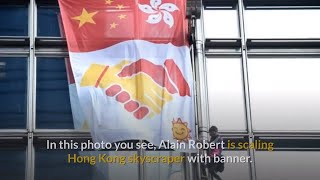 French Spiderman scales Hong Kong skyscraper with banner urging peace