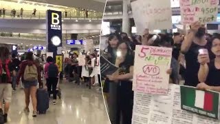 Passengers Walk By Protesters At Hong Kong Airport