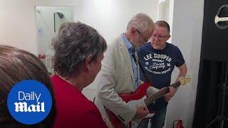 JeremyCorbyn plays guitar during Bolton visit
