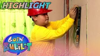 A carpenter helps a man put up a portrait on the wall | Goin' Bulilit
