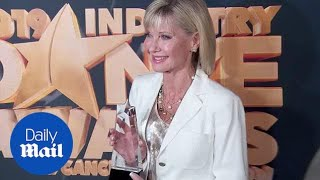 Olivia Newton-John stuns in white suit at cancer benefit show