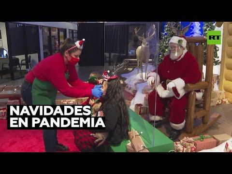 Niños se reúnen con Santa separados por barrera protectora