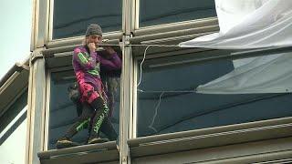 'French Spider-Man' Alain Robert climbs Hong Kong skyscraper and unveils peace banner